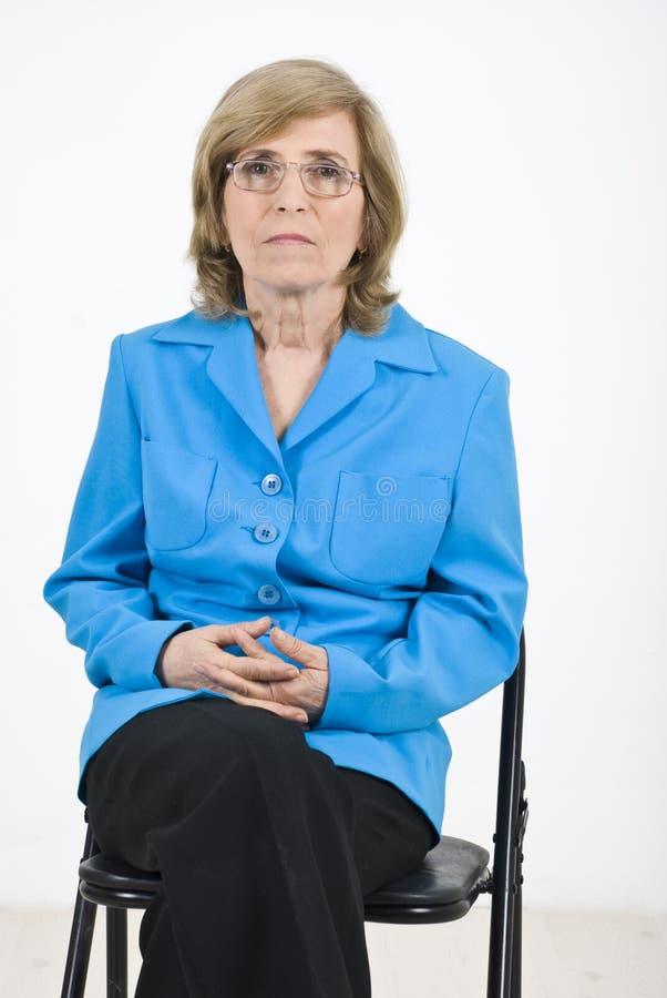Ältere Frau, die auf Stuhl wartet lizenzfreies stockbild