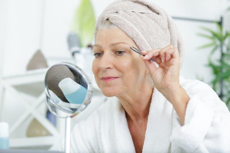 Ältere Frau, die Augenbrauen mit Pinzette zupft lizenzfreie stockfotos