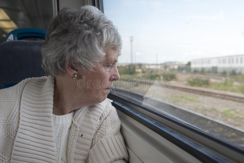 Ältere Frau, die aus dem Fenster auf einem Zug heraus schaut stockfotografie