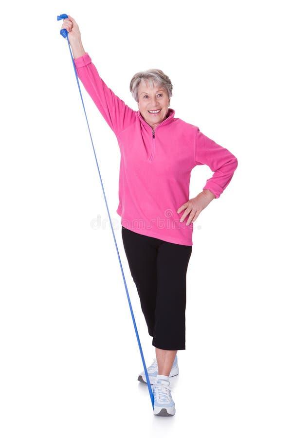 Ältere Frau, die Ausrüstung ausübend ausdehnt stockbild