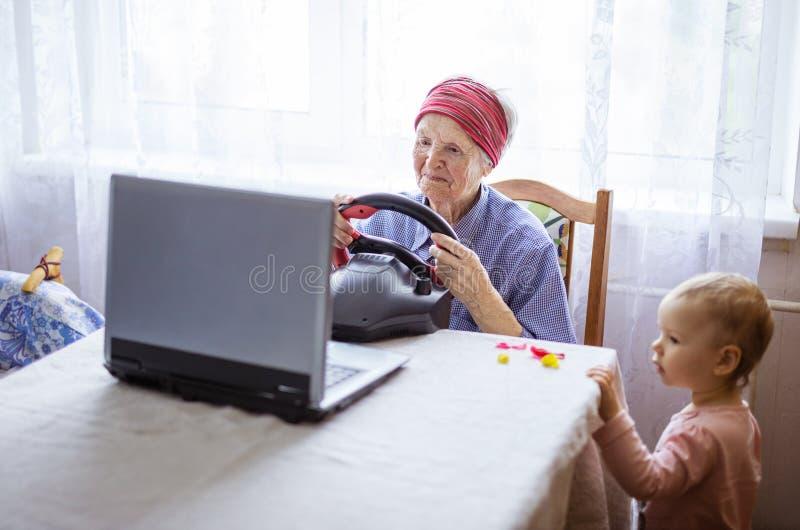 Ältere Frau, die Autorennenvideospiel auf Laptop während ihr großes - Enkelin aufpasst ihr Spiel genießt stockbild