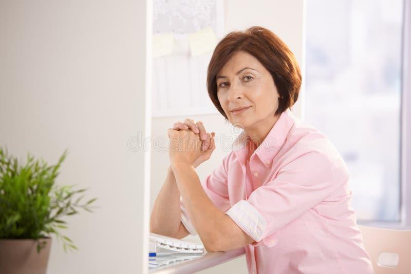 Ältere Frau, die am Büroschreibtisch sitzt lizenzfreies stockbild