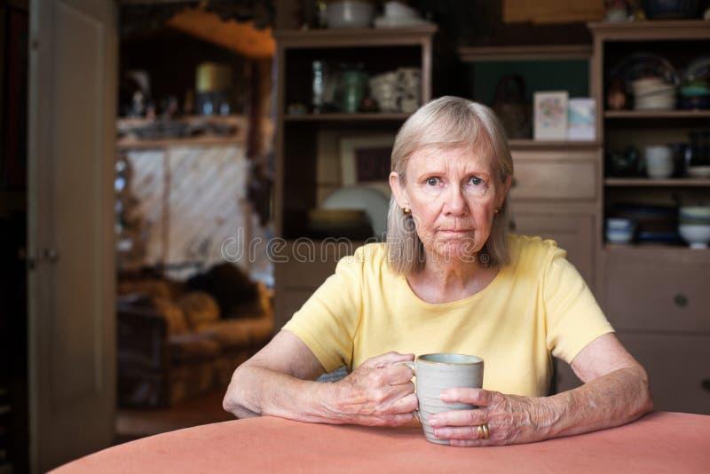 Ältere Frau, die bei Tisch sitzt stockbilder