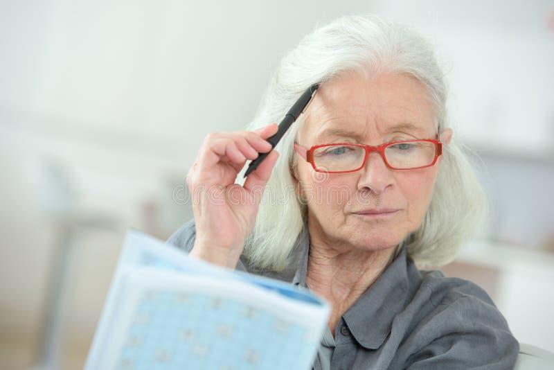 Ältere Frau, die bei Tisch sitzt, Kreuzworträtsel abschließend stockbilder