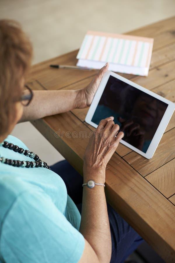 Ältere Frau, die bei Tisch unter Verwendung des Tablet-Computers, erhöht über Schulteransicht, Vertikale sitzt lizenzfreie stockfotografie