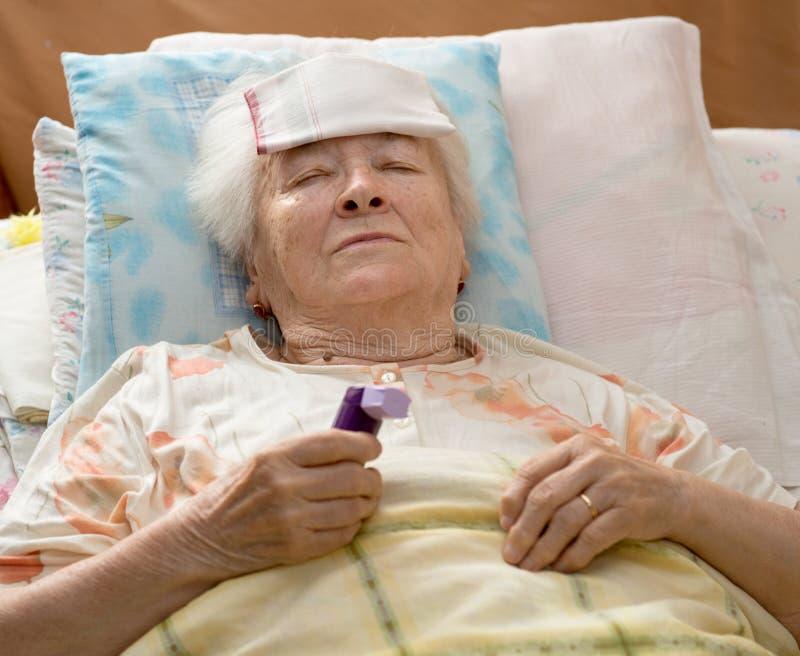 Ältere Frau, die am Bett liegt stockfotos
