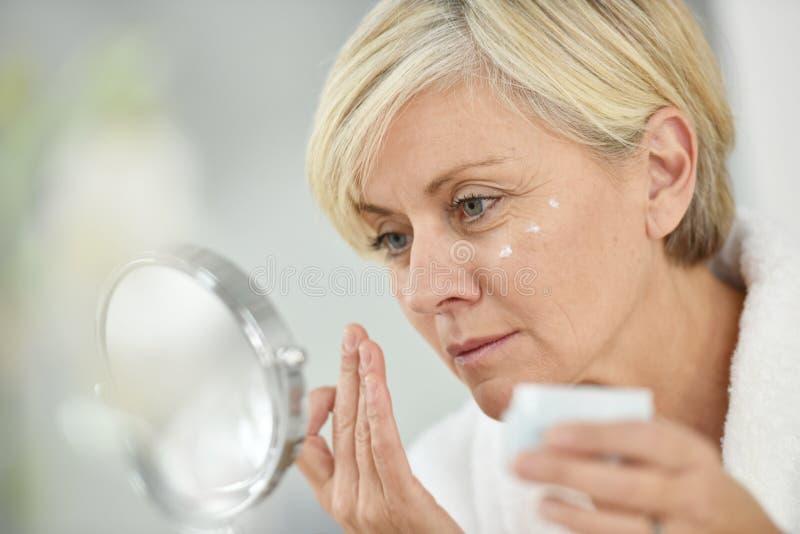 Ältere Frau, die Creme auf ihrem Gesicht aufträgt lizenzfreie stockfotos