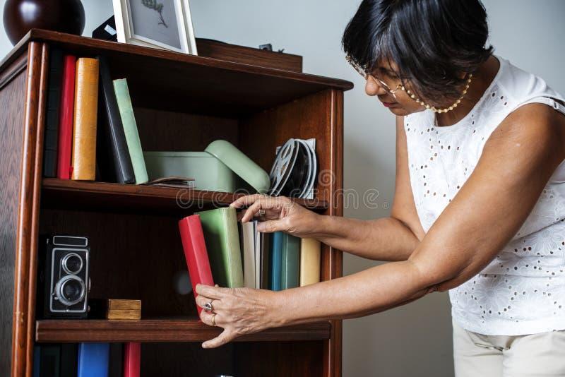 Ältere Frau, die das Bücherregal säubert stockfotos