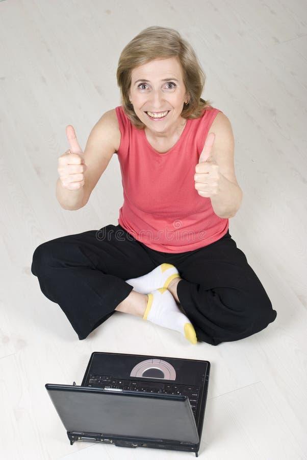 Ältere Frau, die Daumen unter Verwendung des Laptops aufgibt stockbilder