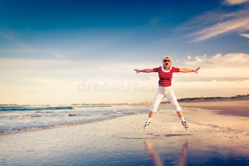 Ältere Frau, die den Strandurlaub springt in einer Luft genießt lizenzfreie stockfotos