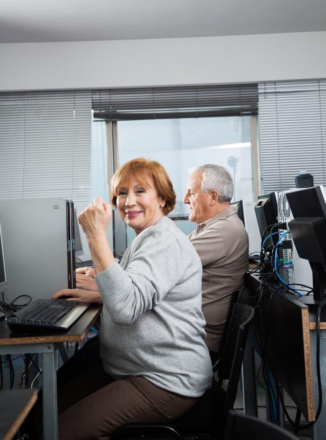Ältere Frau, die in der Computer-Klasse zujubelt lizenzfreie stockfotografie