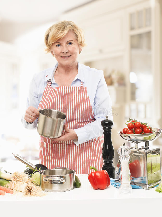 Ältere Frau, die in der Küche kocht stockbilder
