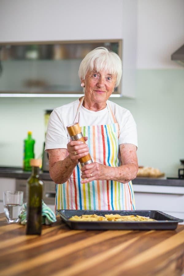 Ältere Frau, die in der Küche - essend und kochend gesund kocht stockfotos