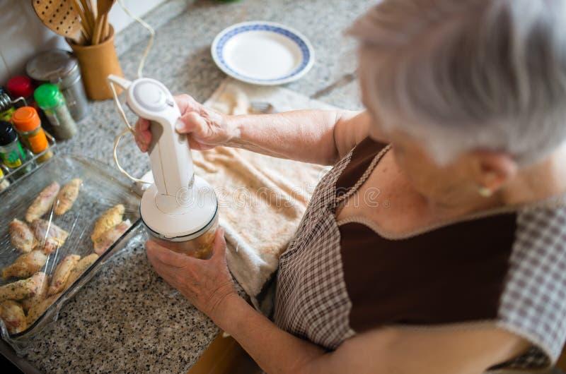 Ältere Frau, die in der Küche kocht stockbild