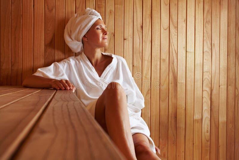 Ältere Frau, die in der Sauna sich entspannt lizenzfreie stockfotografie