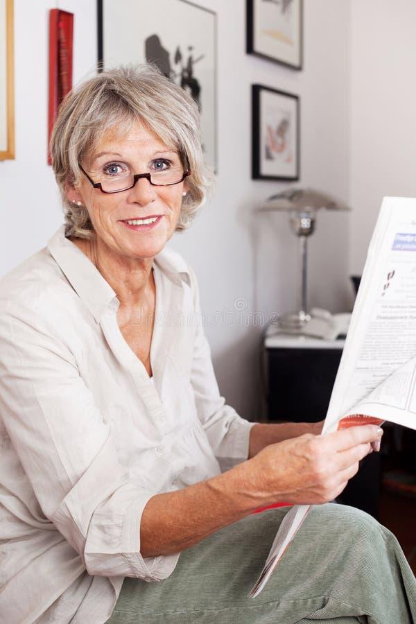 Ältere Frau, die die Zeitung lesend genießt lizenzfreie stockbilder