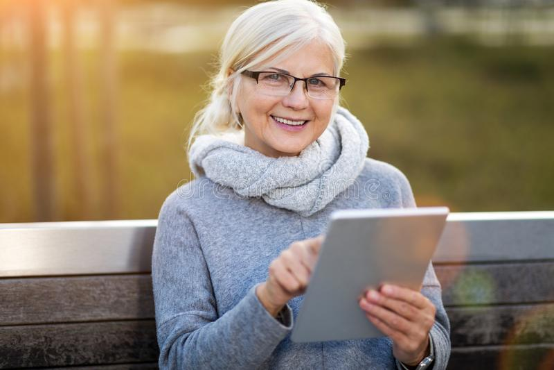 Ältere Frau, die digitale Tablette verwendet lizenzfreie stockfotografie