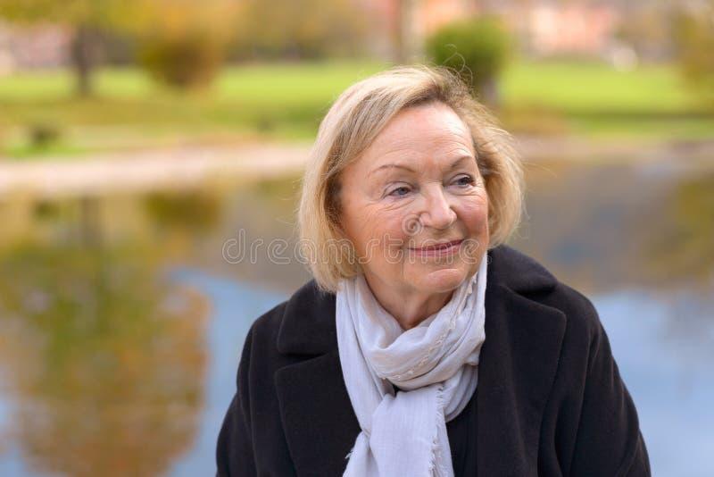 Ältere Frau, die draußen einen Falltag genießt lizenzfreie stockfotografie