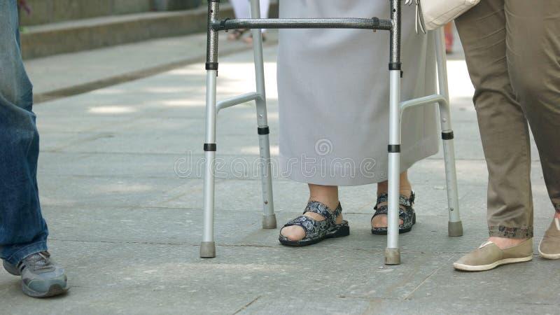Ältere Frau, die draußen mit Metallwanderer geht lizenzfreie stockfotografie