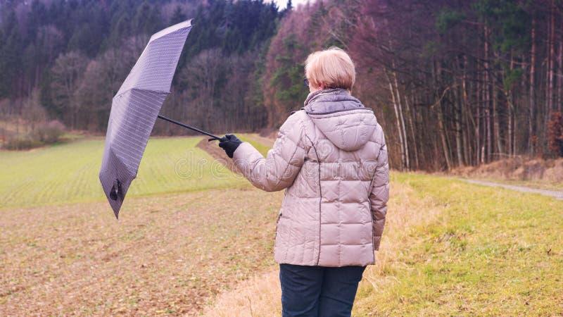 Ältere Frau, die draußen mit Regenschirm steht lizenzfreie stockbilder