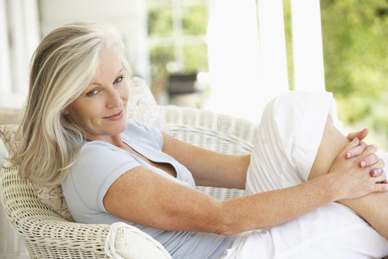 Ältere Frau, die draußen sitzt stockfotografie