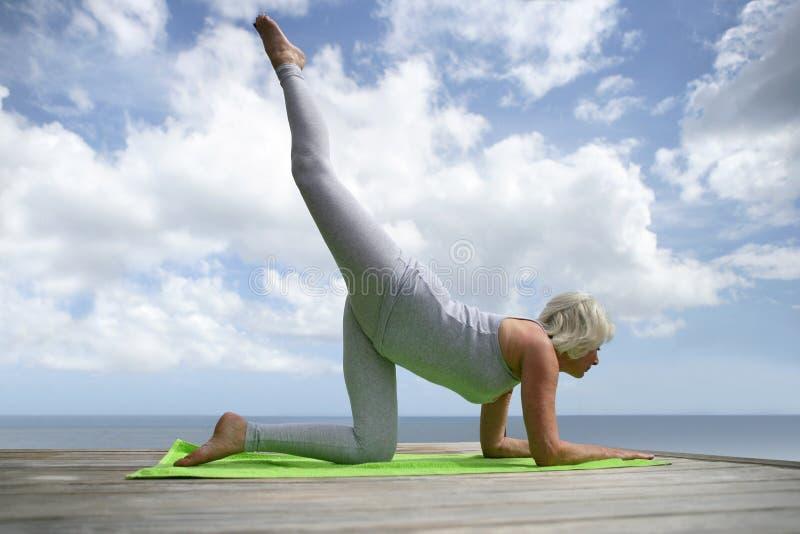 Ältere Frau, die draußen trainiert stockbild