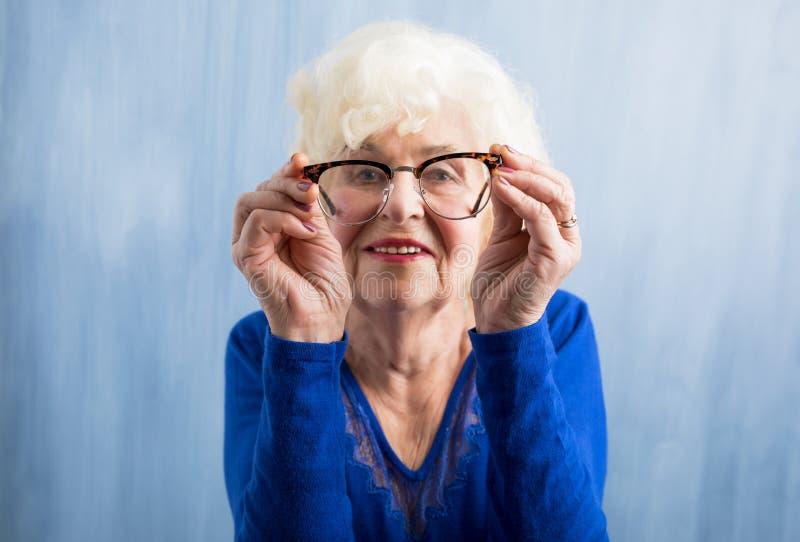 Ältere Frau, die durch Gläser schaut lizenzfreie stockfotos