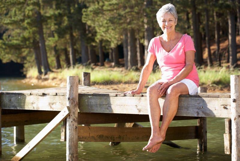 Ältere Frau, die durch See sitzt stockbild