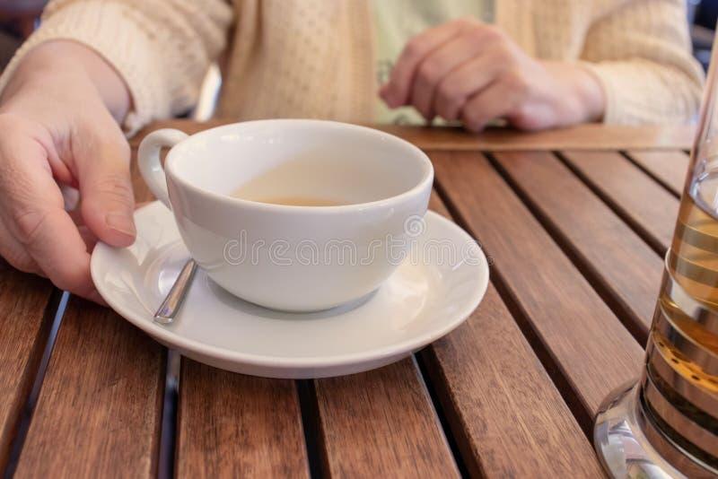 Ältere Frau, die durch die Tabelle sitzt und eine Tasse Tee hält lizenzfreies stockbild