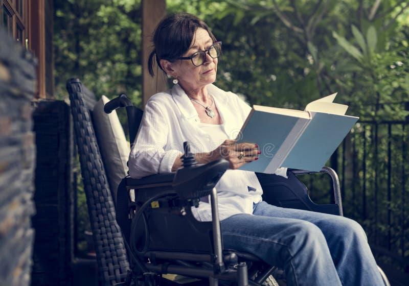 Ältere Frau, die ein Buch in einem Rollstuhl liest lizenzfreie stockfotografie