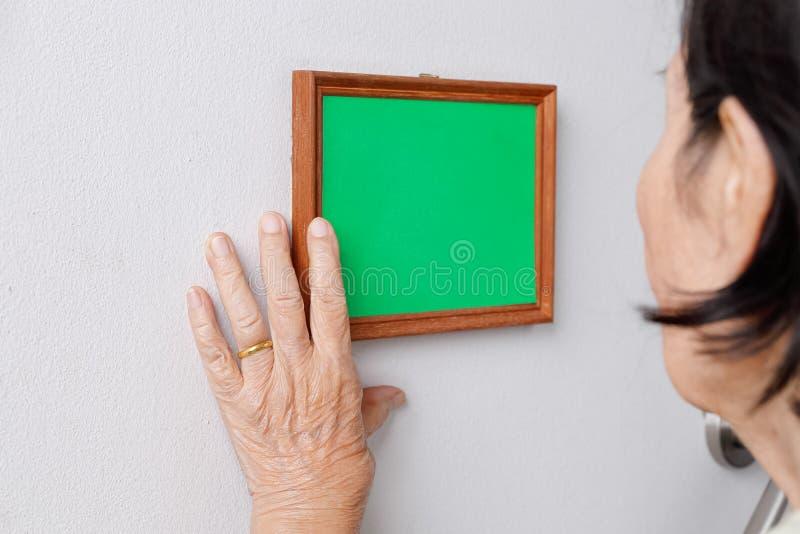 Ältere Frau, die ein Gedächtnisfoto auf Wand betrachtet stockbild
