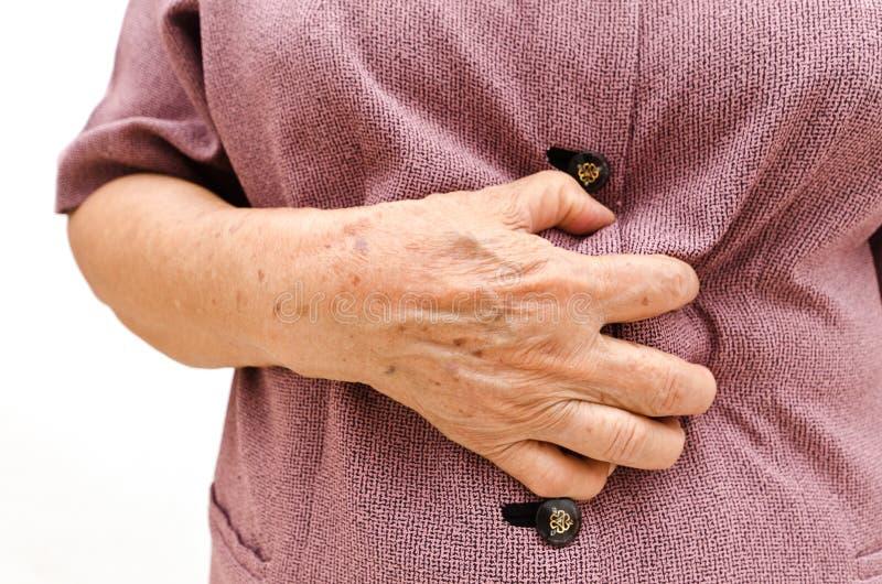 Ältere Frau, die ein stomachache hat lizenzfreies stockfoto