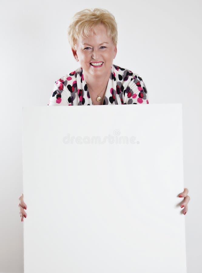 Ältere Frau, die ein unbelegtes weißes Zeichen anhält stockbild