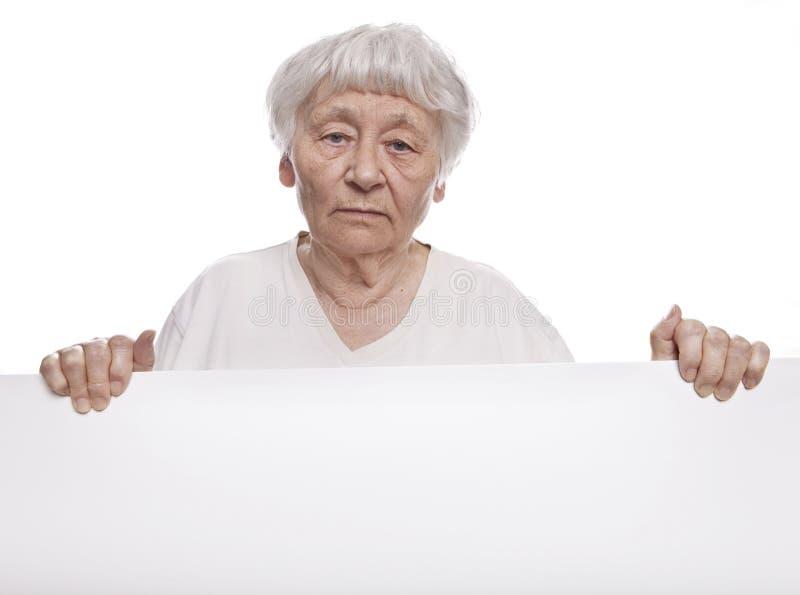 Ältere Frau, die ein unbelegtes Zeichen anhält stockfotos