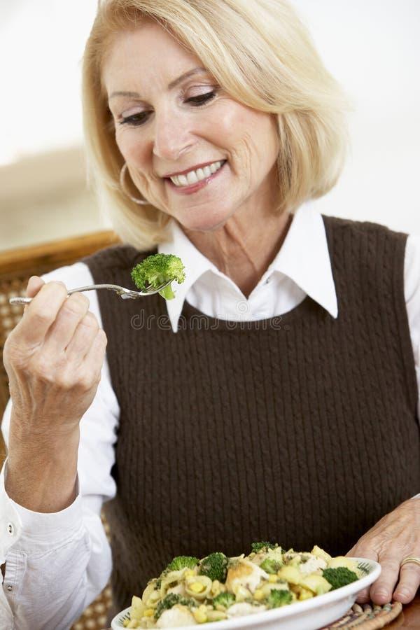 Ältere Frau, die eine gesunde Mahlzeit isst stockfoto