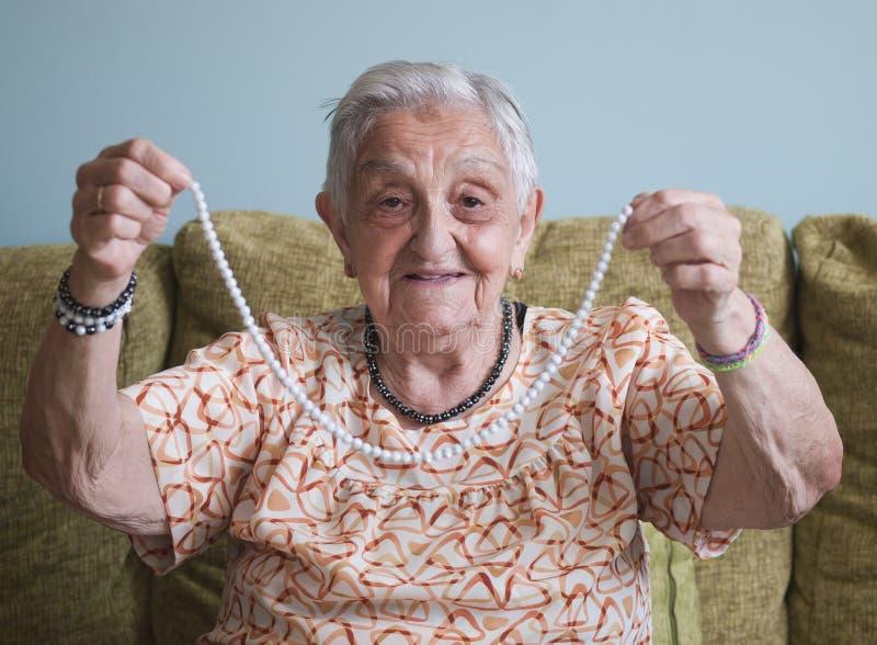 Ältere Frau, die eine Halskette zeigt stockbild