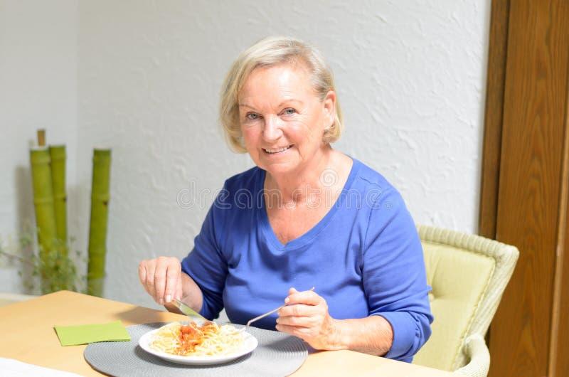 Ältere Frau, die eine Mahlzeit isst stockfotografie