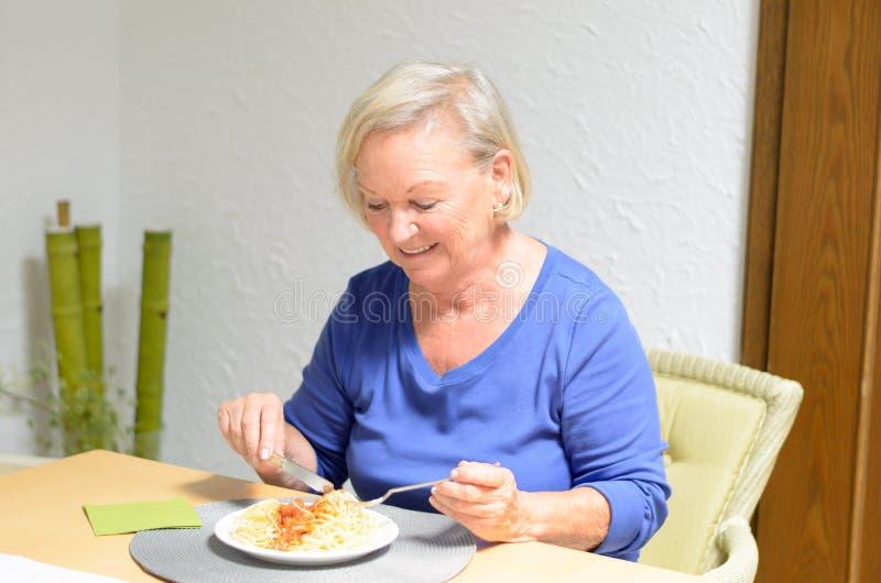 Ältere Frau, die eine Mahlzeit isst lizenzfreie stockfotografie
