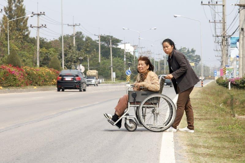 Ältere Frau, die eine Rollstuhlkreuzstraße verwendet lizenzfreie stockfotografie