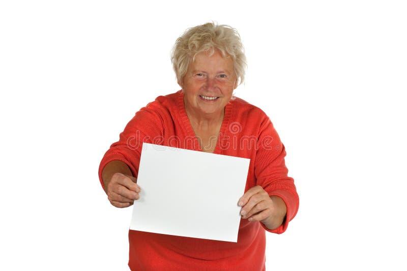 Ältere Frau, die einen unbelegten Vorstand anhält lizenzfreies stockfoto