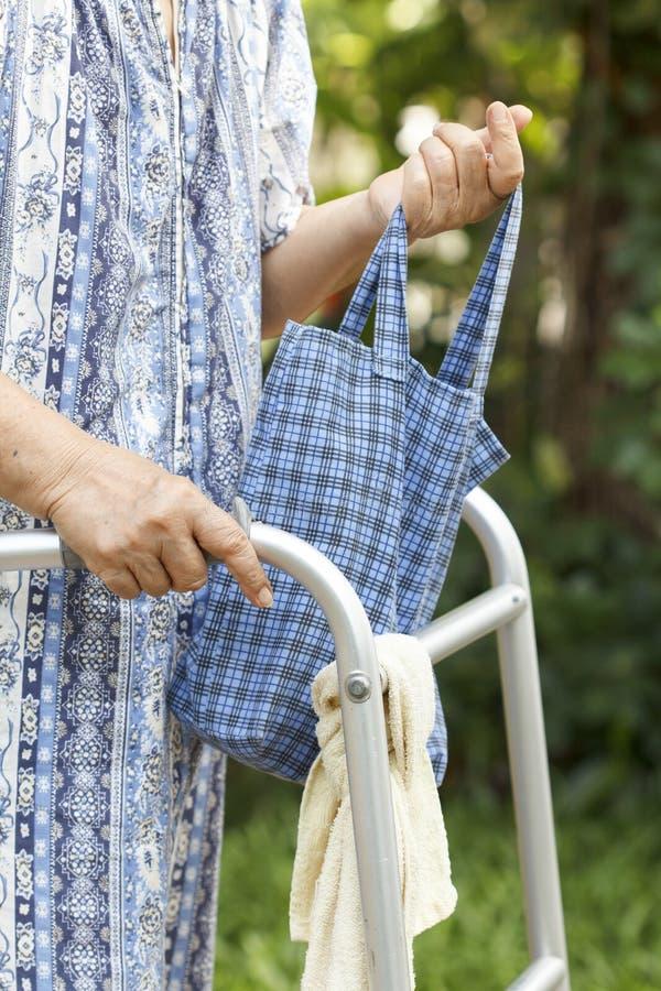 Ältere Frau, die einen Wanderer verwendet stockbild