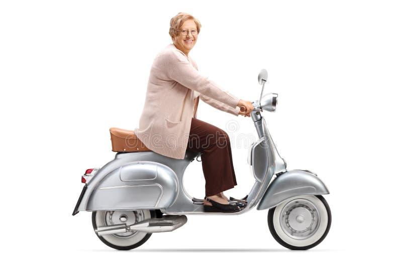 Ältere Frau, die einen Weinleseroller reitet und an der Kamera lächelt stockfotografie
