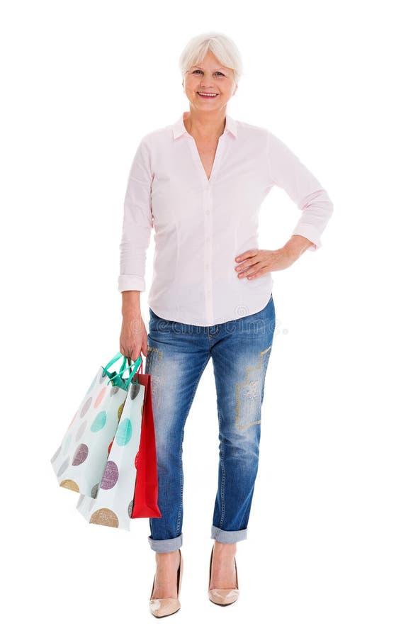 Ältere Frau, die Einkaufstaschen hält lizenzfreies stockbild