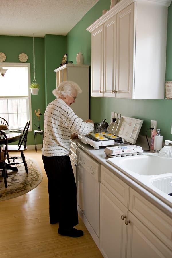 Ältere Frau, die Frühstück kocht stockbilder
