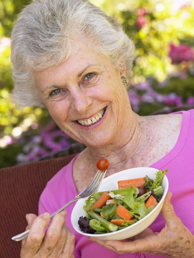 Ältere Frau, die frischen Salat isst stockfotografie