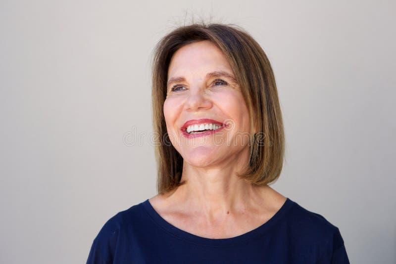 Ältere Frau, die gegen grauen Hintergrund lacht stockbild