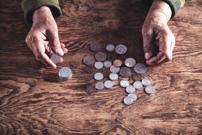 Ältere Frau, die Geld auf Holztisch zählt lizenzfreie stockfotografie