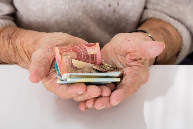 Ältere Frau, die Geld auf Palme zeigt stockbild