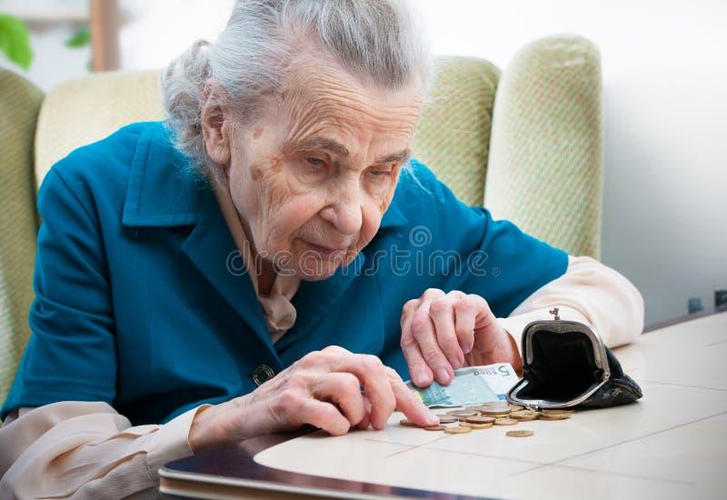 Ältere Frau, die Geld zählt stockbilder