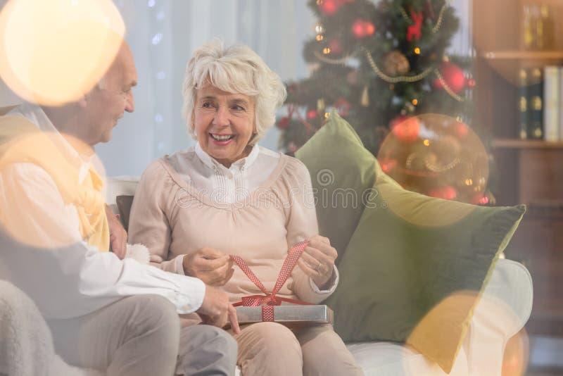 Ältere Frau, die Geschenk vom Ehemann empfängt lizenzfreie stockfotos